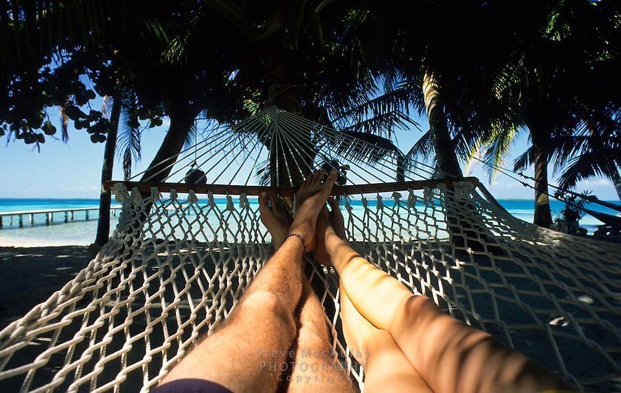 Couple's feet in hammock under palm trees on beach, Belize