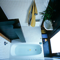 A bird's eye view of the tiled bathroom with a sunken bath from the loo which is located above it