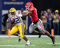 ATLANTA, GA - DECEMBER 7: Clyde Edwards-Helaire #22 of the LSU Tigers attempts to break away from a tackle by Monty Rice #32 of the Georgia Bulldogs during a game between Georgia Bulldogs and LSU Tigers at Mercedes Benz Stadium on December 7, 2019 in Atlanta, Georgia.