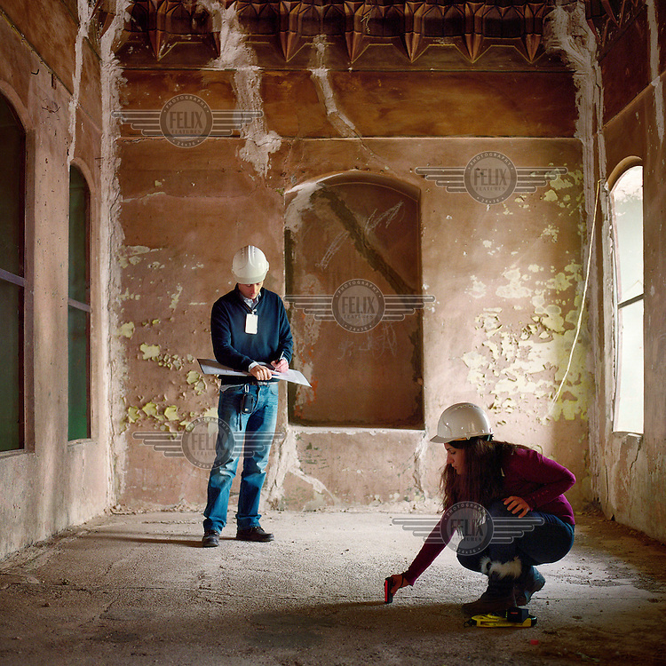 Archaeologists carry out measurements and inspect one of the many semi derelict buildings inside the ancient Citadel of Arbil. The Citadel of Arbil is an inhabited mound in the centre of the modern Iraqi city of Erbil, which is said to be one of the oldest, continually inhabited places in the world. Earliest traces of habitation on the mound date back to the 5th millennium BC, possibly earlier. The city of Erbil, the fourth biggest in Iraq, is today the capital of Iraqi Kurdistan. .Since 2007 the High Commission for Erbil Citadel Revitalisation (HCECR) has been in charge of the Citadel complex and is carrying out major reconstruction efforts since moving out all remaining residents. It is hoped that 50 families will move back into the Citadel once renovation work and archeological digs have been completed. .