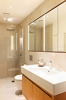 A modern tiled bathroom in neutral tones. The room has a mirror above the washbasin, which is set on a wooden cupboard unit and a separate shower area with a glass screen.