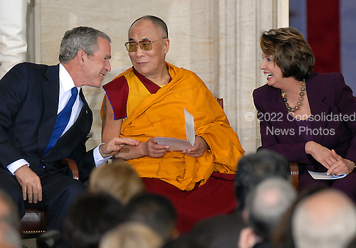 Washington, DC - October 17, 2007 -- United States President George W. Bush, left, The 14th Dalai Lama, Tenzin Gyatso, center, and Speaker of the House Nancy Pelosi (Democrat of California), right, share a light thought during a ceremony where the Dalai Lama accepts the Congressional Gold Medal, the nation's highest and most distinguished civilian award, in Washington, D.C. on Wednesday, October 17, 2007..Credit: Ron Sachs/CNP