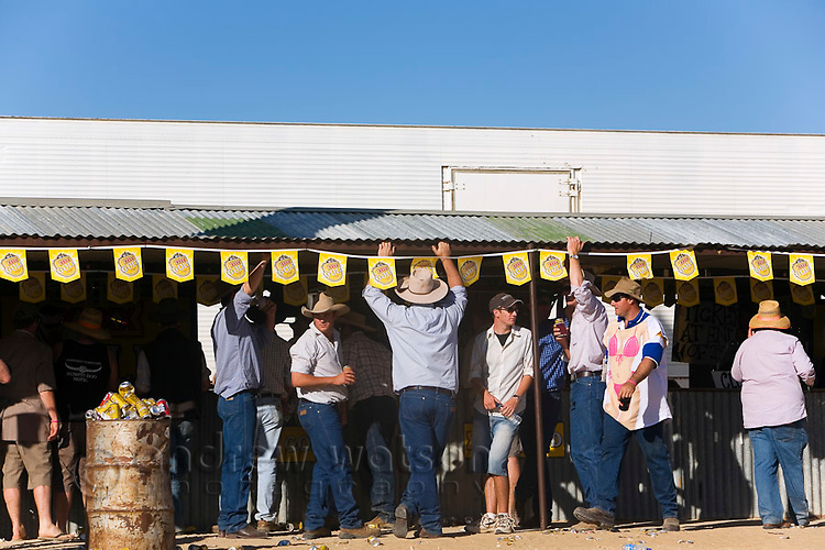 Bush locals drink at the bar during the Birdsville Races.  Every September the remote town of Birdsville comes alive with thousands of visitors for the Birdsville Cup, the most famous horse racing carnival in outback Australia.  Birdsville, Queensland, AUSTRALIA.