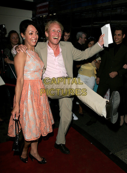 PAUL NICHOLAS & GUEST.Grease - press night, Piccadilly Theatre, London, England..August 8th, 2007.full length beige suit orange sleeveless lace dress arm in air mouth open leg foot kick kicking gesture funny .CAP/AH.©Adam Houghton/Capital Pictures
