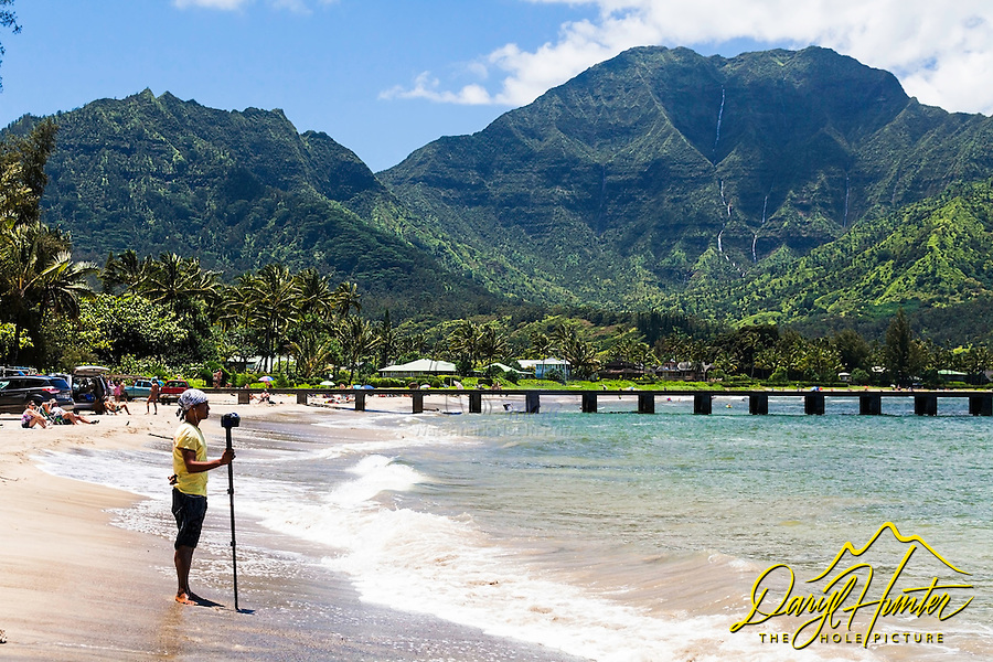 "Hanalei Bay, is the largest bay on Kauai. Hanalei means ""crescent bay"" in Hawaiian. It is a long half moon of golden sand backed by 4,000-foot-high green mountains. Look closely and you may be able to spot several waterfalls."