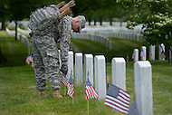 May 23, 2013  (Arlington, Virginia)  A member of the 3rd U.S. Infantry Regiment (the Old Guard), places an American flag before a gravestone at Arlington National Cemetery. The annual tradition, known as Flags In, honors every fallen soldier's grave with a flag.  (Photo by Don Baxter/Media Images International)
