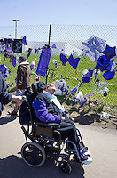 Handicapped man in wheelchair paying homage to Prince at the memorial fence. Paisley Park Studios Chanhassen Minnesota MN USA