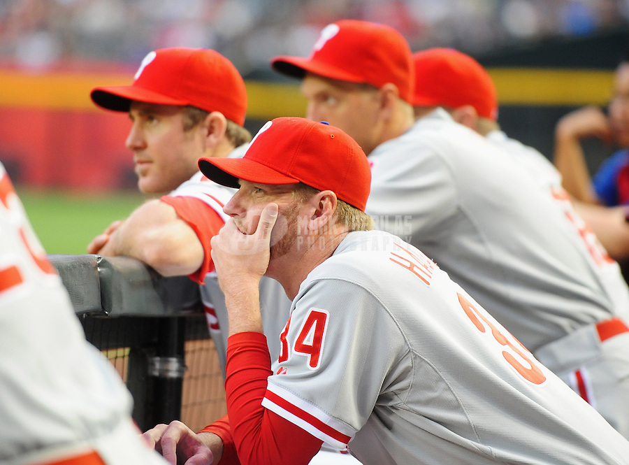 Apr. 23, 2012; Phoenix, AZ, USA; Philadelphia Phillies pitcher Roy Halladay (center) watches from the bench alongside Chase Utley in the first inning against the Arizona Diamondbacks at Chase Field. Mandatory Credit: Mark J. Rebilas-