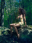 Sensual erotic portrait of a beautiful sexy half naked fairy like woman wearing a revealing summer dress and a wreath sitting a rock in the nature