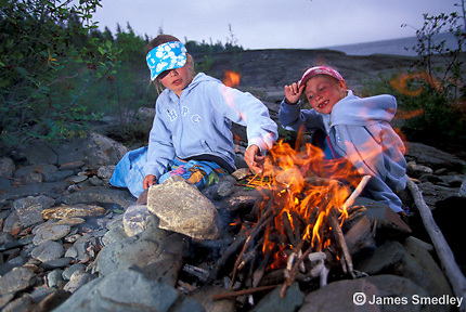 Young girls enjoying a campfire near the lake