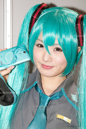 An exhibitor poses for the camera and shows the Hatsune Miku's Xperia product at Tokyo Game Show,  September 20, 2013. The Tokyo Game Show one of the world's biggest trade show for video game developers brings exhibitors from 33 different countries and regions, 352 companies and organizations, opens from September 19 to 22 at the International Convention Complex Makuhari Messe in Chiba. (Photo by Rodrigo Reyes Marin/AFLO)