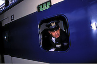 "A driver looks out of the window of a shinkansen ""bullet train"" in Tokyo, Japan. The Bullet train could be thought of as the world's first speed train. Services started in 1964 with speeds at 210km/h or 131mph, the fastest trains went at the time, and many countries stills have no trains running at this speed."