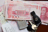 Chinese businessman's currency, one hundred Yuan bills, and receipts with Mercedes car key and mobile phone.
