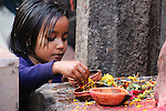 A young girl makes an offering to one of the many gods surrounding the Kamakhya Temple at Guwahati.