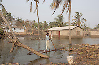 Ghana - Fuveme - A young boy sails back home on a piece of wood after the high tide has flooded the village.<br /> Nestled between the ocean and the Volta river estuary, the village of Fuvemeh has seen its territory reduced from several kilometers to few hundred meters. Nowadays, the villages sits on a narrow strip of land which separates the coastline from the adjacent lagoon. Haunted by coastal erosion, its 1,000 inhabitants have literally nowhere to move.