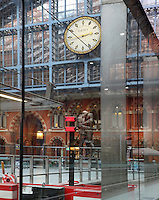 "St Pancras International seen through window panels, 19th century railways' terminus celebrated for its Victorian architecture, ""The Meeting Place"", by Paul Day, 2007, and the famous St. Pancras Clock which has been re constructed by the original makers Dent and now hangs high in the apex of the Barlow shed, London, UK. Picture by Manuel Cohen"