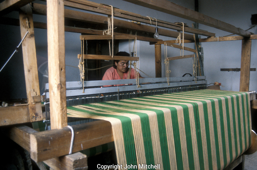 Man weaving on a treddle loom in the Casa de los Once Patios or House of the Eleven Patios in Patzcuaro, Michoacan, Mexico. This former Dominican convent now houses a handicrafts workshops and boutiques.
