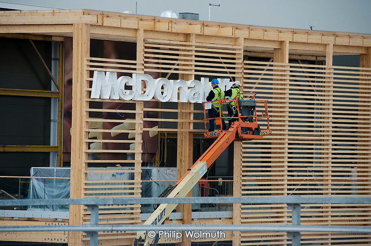 Workmen attach a McDonald's sign onto a branch of the fast food chain in the Olympic Park, London.