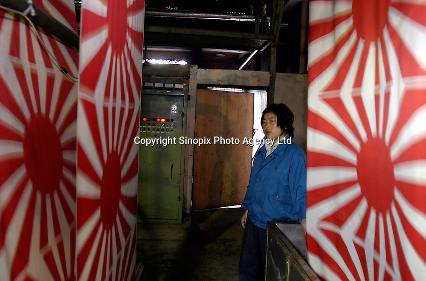 A workers stands by a sheet of Japanese military flags at the Shanghai Flag Factory in Shanghai, China. A majority of flags used around the world are produced in China due to its low costs, however state-owned factory like this one are out competed by smaller private firms who are more flexible and cheaper..26-APR-04