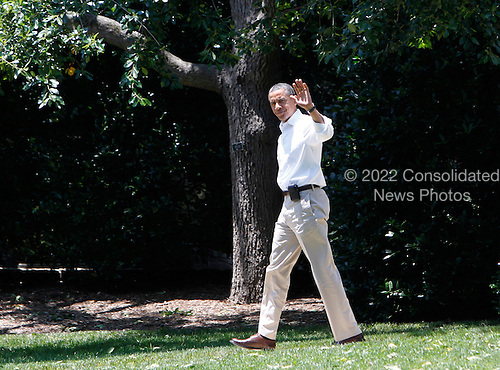 United States President Barack Obama waves as he walks across the South Lawn of the White House prior to his departure aboard Marine One for Camp David, the Presidential Retreat, on June 30, 2012.  .Credit: Dennis Brack / Pool via CNP