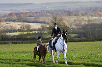 Mother and daughter ride together through rolling hillsides, The Cotswolds, Oxfordshire, United Kingdom