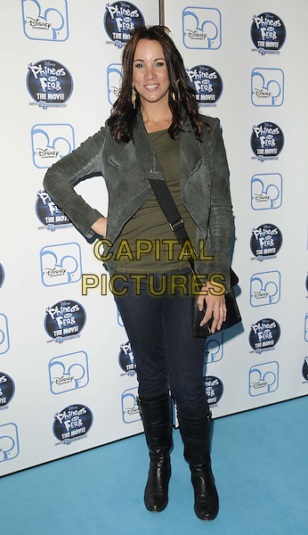 "ANDREA McLEAN.At the UK premiere of Disney's ""Phineas and Ferb the Movie: Across the 2nd Dimension"" at Appollo Picadilly, London, England..24th September 2011.full length black jacket jeans denim green top hand on hip grey gray .CAP/CAN.©Can Nguyen/Capital Pictures."