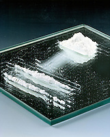 STILL LIFE: NEGATIVE IMAGE OF COCAINE<br /> Pile of Addictive Substance Cocaine on mirrored surface. Cocaine appearing in powder form is a salt, typically cocaine hydrochloride.