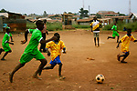 Two boys go for the ball during a soccer game at Hamomi Children's Centre in Nairobi, Kenya