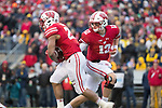Wisconsin Badgers quarterback Alex Hornibrook (12) hands the ball off to running back Jonathan Taylor (23) during an NCAA College Big Ten Conference football game against the Michigan Wolverines Saturday, November 18, 2017, in Madison, Wis. The Badgers won 24-10. (Photo by David Stluka)