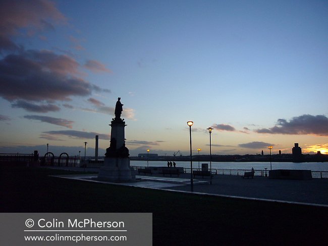 Sun setting over statues and a war memorial at the Pierhead on the river Mersey in Liverpool. The river separated the port city of Liverpool from the peninsula of Wirral to the south. Liverpool was chosen to be European Capital of Culture for 2008.