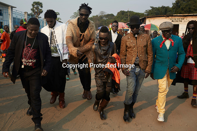 """KINSHASA, DEMOCRATIC REPUBLIC OF CONGO - July 16: Sapeurs from the group Leopard de la Sape walk the streets on July 16, 2014, in Kinshasa, DRC. The word Sapeur comes from SAPE, a French acronym for Société des Ambianceurs et Persons Élégants or Society of Revellers and Elegant People and it also means, to dress with elegance and style"""". Most of the young Sapeurs are unemployed, poor and live in harsh conditions in Kinshasa, a city of about 10 million people. For many of them being a Sapeur means they can escape their daily struggles and dress like fashionable Europeans. Many hustle to build up their expensive collections. Most Sapeurs could never afford to visit Paris, and usually relatives send or bring clothes back to Kinshasa. (Photo by Per-Anders Pettersson)"""
