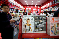 Shoppers in Shanghai magazine shop, China. Victoria Beckham, Posh Spice, on cover of Chinese magazine.