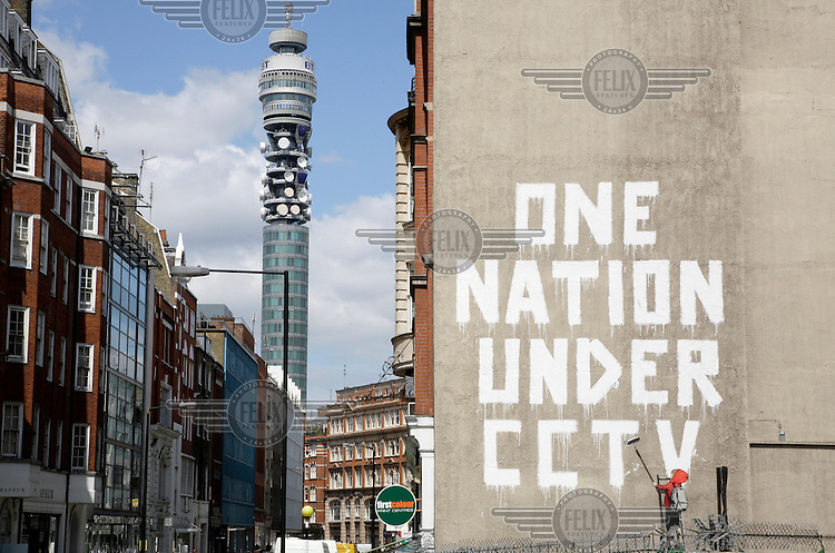 The BT Tower stands beside work by graffiti artist Banksy, bemoaning the rise of CCTV, on Newman Street in London's West End.