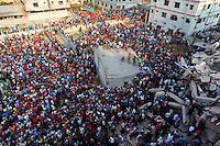 A large crowd of onlookers gathers in front of the collapsed Rana Plaza complex in Savar. The 8 storey building, which housed a number of garment factories employing over 3,000 workers, collapsed on 24 April 2013. By 29 April, at least 380 were known to have died while hundreds remained missing. Workers who were worried about going to work in the building when they noticed cracks in the walls were told not to worry by the building's owner, Mohammed Sohel Rana, who is a member of the ruling Awami League's youth front. He fled his home and tried to escape to neighbouring India after the building collapsed but was caught by police and brought back to Dhaka. Some of the factories working in the Rana Plaza building produce cheap clothes for various European retailers including Primark in the UK and Mango, a Spanish label. . /Felix Features