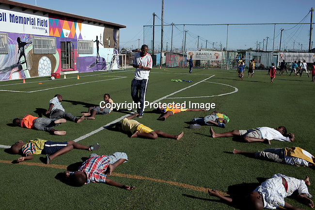 Khayelitsha, South Africa March 11, 2013: Luyanda Hans, a Senior leader, holds a skills training session at Amandla EduFootball which was founded by Jakob Schlichti and Florian Zech in the field in Khayelitsha a poor township outside Cape Town, South Africa. They use football to initiate, support educational projects for youth in the township. The program keep children busy and it decreases the risk of them joining gang, criminal activity or teenage pregnancy. The crime level has decreased substantially in the area since the program was created in 2006. (Photo by: Per-Anders Pettersson)