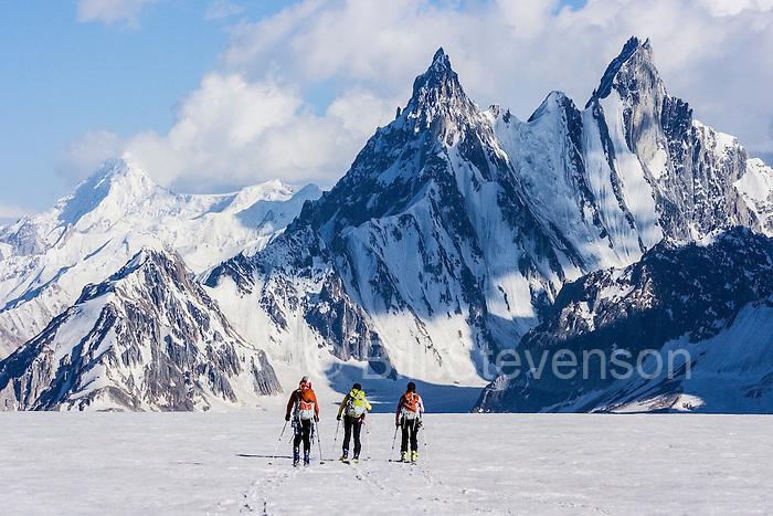 Three people skiing on the Biafo glacier in the Karakoram himalaya in Pakistan