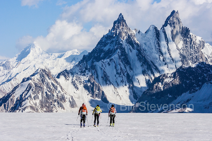 Three people skiing on the Biafo glacier in the Karakoram himalaya in Pakistan