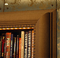 The bookcases in the drawing room are covered in a brown tweed and framed by antique mirrored panels
