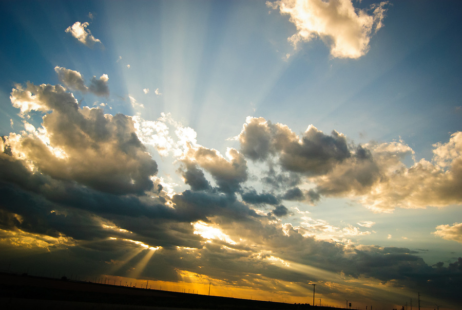 Sun rays piercing clouds over a West Texas landscape at sunset.