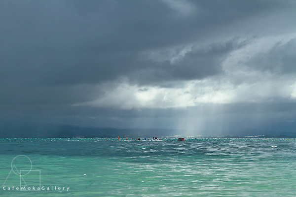 Ilet de Gosier looking towards Basse Terre on a stormy day with swimmers in the distance
