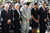 Fort Hood, TX - November 10, 2009 -- U.S. President Barack Obama (R), First Lady Michelle Obama (2-R), Lieutenant General Robert Cone (C), unidentified woman (2-L) and Defense Secretary Robert Gates (L) bow their heads during a prayer at the memorial service for the 12 soldiers and one civilian killed at Fort Hood U.S Army Post near Killeen, Texas, USA 10 November 2009. Army Major Malik Nadal Hasan reportedly shot and killed 13 people, 12 soldiers and one civilian, and wounded 30 others in a rampage 05 November at the base's Soldier Readiness Center where deploying and returning soldiers undergo medical screenings.  .Credit: Tannen Maury / Pool via CNP