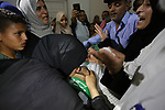 Relatives of Palestinian Mohammed Abu Daqqa, 24, who died of wounds he sustained during clashes with Israeli troops, mourn over his body during his funeral in Khan Younis in the southern Gaza Strip on June 21, 2018. Photo by Ashraf Amra