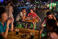 A couple eats lamb and chicken skewers and drinks beer from a food stall near the carnival at Yangrenjie, or Meixin Foreigner Street, a sprawling amusement and oddity park in northeastern Chongqing, China. Park is popular among lower-class Chongqingers. Meat skewers cost 1RMB per skewer.