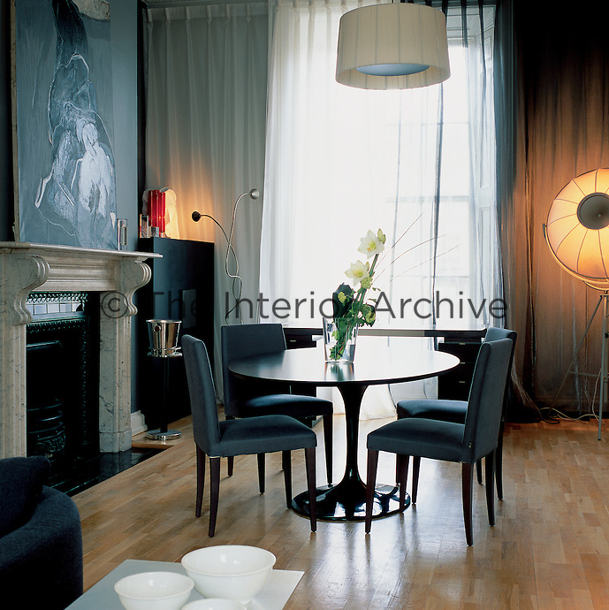 A dining room with a traditional fireplace and furnished in a contemporary way. The dark oak cabinet to the right of the fireplace is by Casamilano; the desk in the window is dark-stained sycamore with a leather inset by Highes Chevalier. The dining area has a black lacquer table by Eero Saarinen and classic upholstered dining chairs.