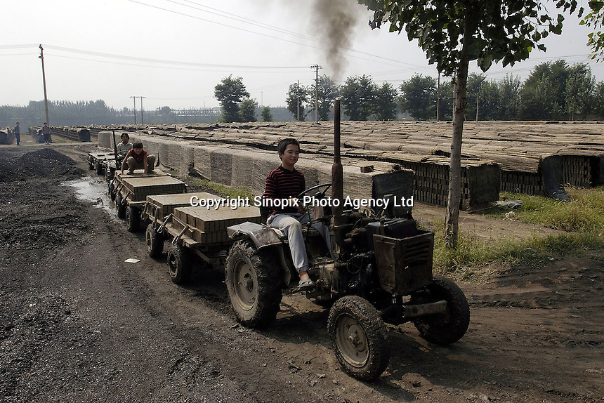 A boy drives tractor to convey the clay bicks  at a brick factory in Bazhou, Hebei province, China..04-SEP-04