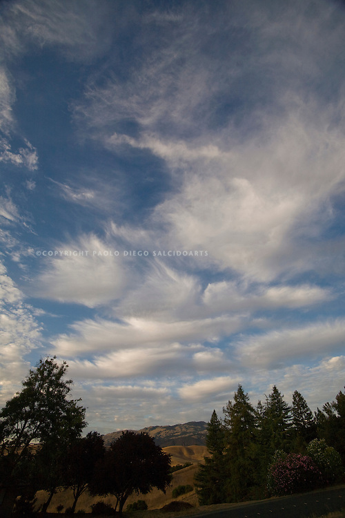 wide angle photograph of landscape by Paolo Diego Salcido of clouds in blue sky.