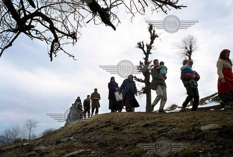 Ethnic Albanian families leave the woods below Gajre where they had been hiding for three days from Serb shelling of their villages. The UNHCR moved them to a safer place in the village of BOB.