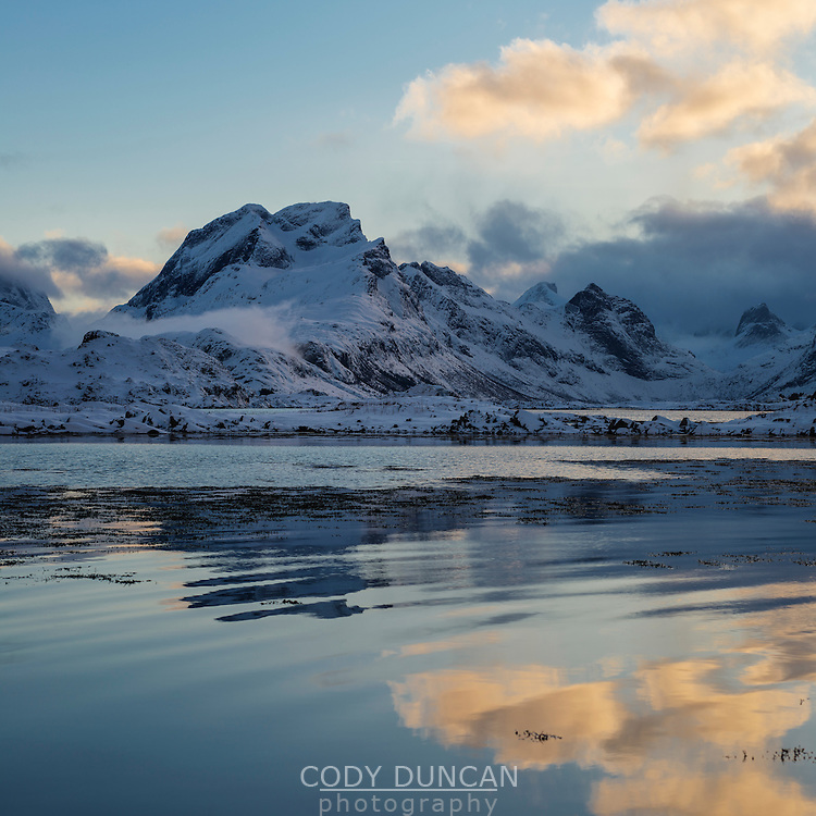 Narvtind mountain peak rises over fjord in winter, Moskenesøy, Lofoten Islands, Norway