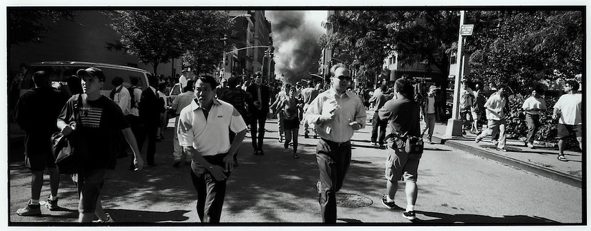 USA. NYC. 9/11/2001. Pedestrians run up West Broadway from falling debris as first tower of the World Trade Center collapses after terrorist attack.