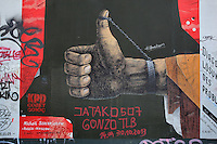 Section of the Berlin Wall depicting a painting by Michail Serebrjakow entitled Diagonale Losung, with a raised thumb chained to a wrist, damaged by graffiti, part of the East Side Gallery, a 1.3km long section of the Wall on Muhlenstrasse painted in 1990 on its Eastern side by 105 artists from around the world, Berlin, Germany. Picture by Manuel Cohen